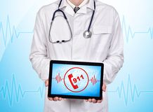 Touch pad with 911 symbol. Doctor holding touch pad with 911 symbol on a blue background Stock Photo