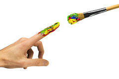 Touch between finger and the paintbrush. Touch between painted finger and the paintbrush Stock Photo