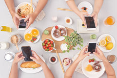 Always in touch. People texting when having lunch together, view from above stock image