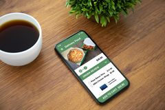 Touch phone with app delivery food on the screen. On the table in the office royalty free stock photography