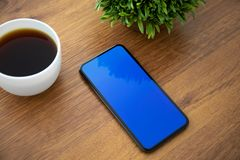 Touch phone with blue screen on the table in office. Touch phone with blue screen is on the table in the office stock images