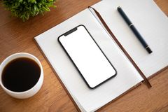 Touch phone with isolated screen on a notebook in the office stock photo