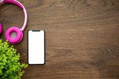 Touch phone with screen on a wooden table with headphones stock photography