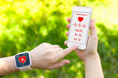 Touch phone and smart watch with mobile app health sensor. Female hands holding touch phone and smart watch with mobile app health sensor stock photography