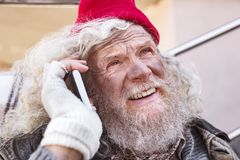 Portrait of a cheerful homeless man. In touch. Portrait of a cheerful homeless man making a phone call Stock Photography