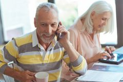 Cheerful aged man talking on phone Royalty Free Stock Images