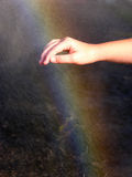 Touch the rainbow. A hand reaching to touch a rainbow in the water spray Royalty Free Stock Image
