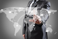 Touch screen. Businessman pushing mail on world map on a touch screen interface Royalty Free Stock Photos