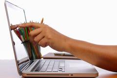 Touch screen del dito e della mano sul monitor un computer portatile su una tavola di legno Fotografie Stock