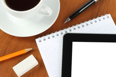 Touch screen device, notepad, pen and coffee cup Stock Photography