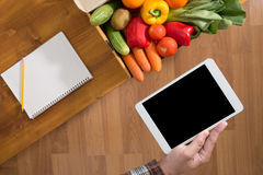 Touch screen digital tablet, fresh vegetables Royalty Free Stock Image