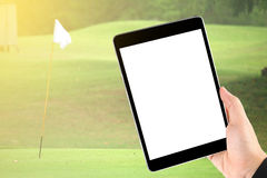 Touch screen in hand, tablet on golf club - soft blur background Stock Images