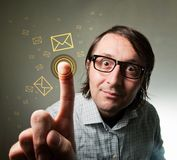 Touch-screen mail inbox. Nerd looking male using a touch screen to check his e-mail inbox, pressing an envelope representing an incoming e-mail message stock photo
