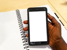 Touch screen mobile phone, in African woman`s hand. Black Female in office holding smartphone using electronic gadget notebook royalty free stock image