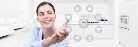 Touch screen sorridente della mano della donna di automazione della casa astuta con bianco fotografia stock libera da diritti