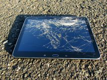 Touch screen tablet with broken screen lying on asphalt road stock photography