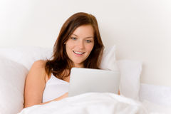 Touch screen tablet computer - woman in bed. Touch screen tablet computer - woman in white bed Royalty Free Stock Photos
