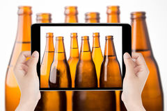 Touch screen tablet in hand a photography the beer bottles. Stock Photos