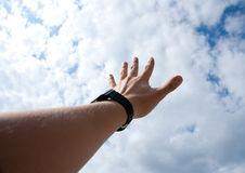 Touch the sky. Male left arm touch sky with white cloudscape Royalty Free Stock Image