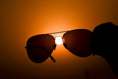 Touch the Sun. Sunglass and hand in Backlit stock photography