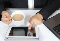 Touch tablet. Business man touch tablet and drink hot coffee on white table Royalty Free Stock Images