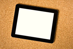 Touch tablet on cork board Royalty Free Stock Photo