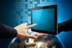 Touch the tablet on earth Royalty Free Stock Image