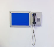 Touch-tone telephone. With information sign on wall Stock Image