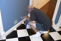 Touch Up Paint. Man holding paint brush touching up paint on wall Royalty Free Stock Images