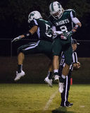 Touchdown Celebration. Two players celebrate after scoring a touchdown.  Shasta College (green) played against Mendocino College   (white) September 13th, 2014 Royalty Free Stock Image