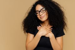 Touched lovely female with Afro hairstyle, keeps both palms on chest, has eyes shut from pleasure, hears heart piercing story,. Wears spectacles and casual t royalty free stock images