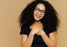 Touched lovely woman with curly hairstyle, keeps palms on chest, tilts head, has charming smile on face, wears optical glasses,. Black casual t shirt, models royalty free stock photo