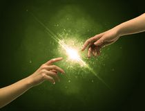 Touching arms lighting spark at fingertip. Two naked male hands about to touch, lighting the spark with modest explosion in front of green background concept Royalty Free Stock Images