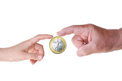 Touching the Euro. The finger of a child and that of an old man while touching (and sharing) a coin of one euro Royalty Free Stock Photography