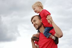Touching family moments. Cute toddler boy sitting on his father`s shoulders. They are smiling, laughing and looking happy. royalty free stock photography