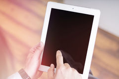 Touching finger in digital touchpad inside a room on a wooden table Royalty Free Stock Photography
