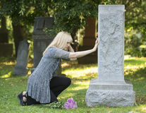 Touching Grief in the Cemetery. Woman mourns with her hand on headstone in cemetery stock photos