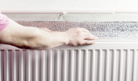 Touching hands to section aluminum radiator Royalty Free Stock Images