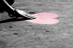 Touching hearts?. Street painter in London drawing a heart on the pavement Stock Image