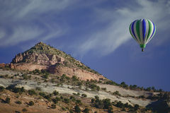 Touching the hilltops. Colorful Hot Air Balloon floating by a hilltop Stock Images