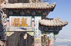 Touching the Luck Charm. A tourist reaches up to touch the good luck stone at the base of Dragon Gate on West Mountain in Kunming, Yunnan province, China stock photography