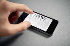 Touching News On Mobile Smartphone. Man hand touch screen with news on contemporary mobile phone. Added a slight vignetting for dramatic effect and focus on the Stock Images