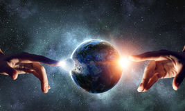 Touching planet with finger. Female hand touching Earth symbolizing faith and religion. Elements of this iamge are furnished by NASA royalty free stock photos