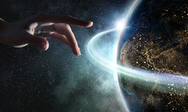 Touching planet with finger. Female hand touching Earth symbolizing faith and religion. Elements of this iamge are furnished by NASA royalty free stock image