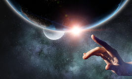 Touching planet with finger. Female hand touching Earth symbolizing faith and religion. Elements of this iamge are furnished by NASA royalty free stock images
