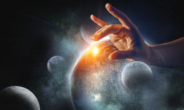 Touching planet with finger. Female hand touching Earth symbolizing faith and religion. Elements of this iamge are furnished by NASA stock images