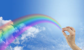 Touching a rainbow in the sky with fingers Stock Photography