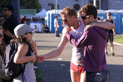 Touching San Francisco Pride Moment. Two flamboyant gay men, one wearing tight red underwear, talk with a woman during the June 2010 Gay Pride weekend in San Royalty Free Stock Photography