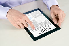 Touching Screen With News On Tablet PC. Businessman hands are pointing on contemporary tablet pc with latest news Royalty Free Stock Photos