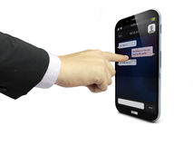 Touching a smartphone with chat app on the screen. Businessman hand touching a smartphone with chat app on the screen Royalty Free Stock Photos